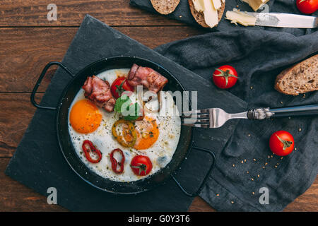 Fried eggs, bacon and cherry tomatoes with bread - Stock Photo