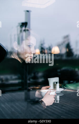 Woman drinking coffee in caf�� - Stock Photo