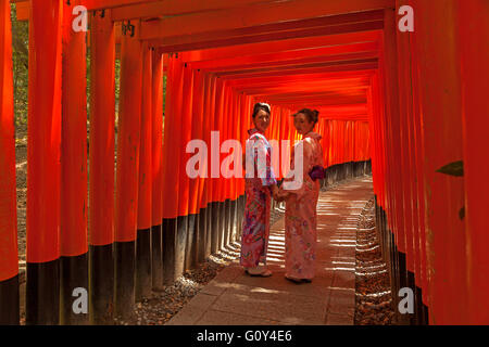 Two women in Kimono by the Fushimi Inari Torii in Kyoto, Japan. - Stock Photo