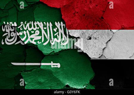 flags of Saudi Arabia and Yemen painted on cracked wall - Stock Photo