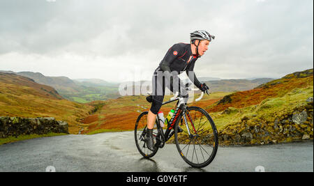 Rider ascending Hardknott Pass during the Fred Whitton Challenge, a 180km/112 mile sportive ride in the English - Stock Photo