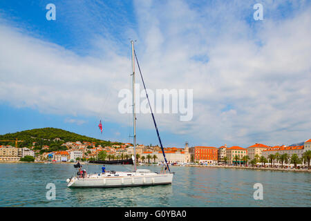 Split, Dalmatian Coast, Croatia.  Yacht coming in to anchor in the harbour. - Stock Photo