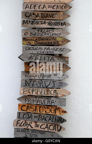 Rustic wooden signs in town centre giving directions to local businesses, Caminha, Minho Province, northern Portugal - Stock Photo