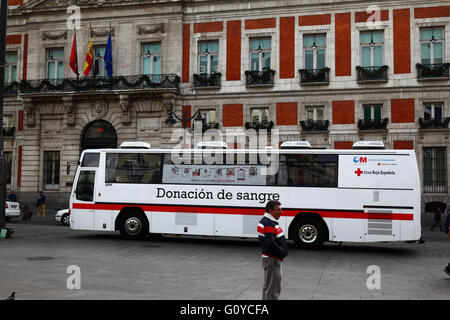 Bus for people to donate blood in front of House of the Post Office / Casa de Correos, Plaza Puerta del Sol, Madrid, - Stock Photo