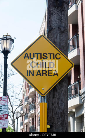 Yellow sign in a US city residential street cautioning drivers about an autistic child in the area - Stock Photo