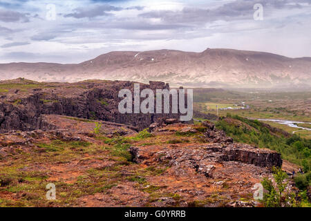 Southwest Iceland, Iceland. 4th Aug, 2015. A view over the top of famous Almannagja canyon in Thingvellir National - Stock Photo