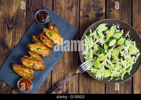 Chicken wings on a slate plate and salad on wooden background - Stock Photo