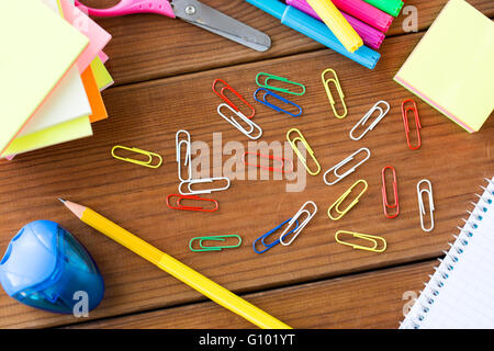 close up of clips, pens and stickers on wood - Stock Photo