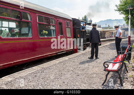 Volunteer workers for Peak Rail, a heritage railway, watch as a steam train is departing at Matlock Railway Station, - Stock Photo