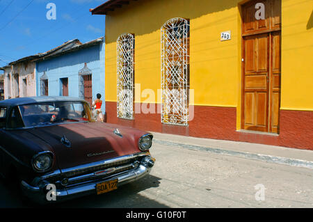 Colourful houses in a street scene. Old red Chevrolet Classic American car parked on a street with traditional, - Stock Photo
