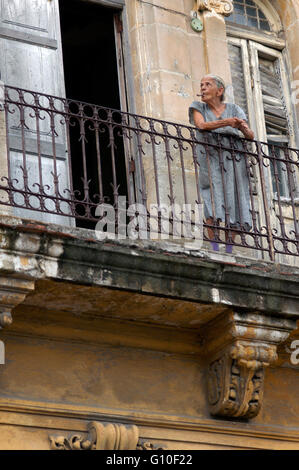 Old woman smoke a cigar in the balcony in a building in poor condition in Havana Vieja, Cuba. - Stock Photo