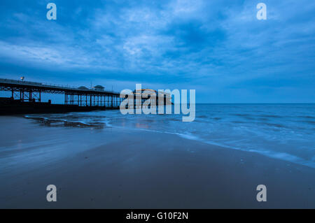 Cloudy evening at Cromer Pier, Norfolk as the sun sets - Stock Photo