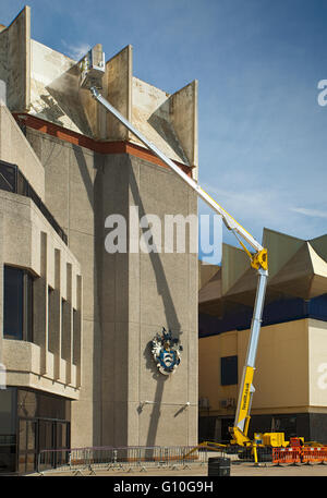 Cherry picker working on a building facade. - Stock Photo