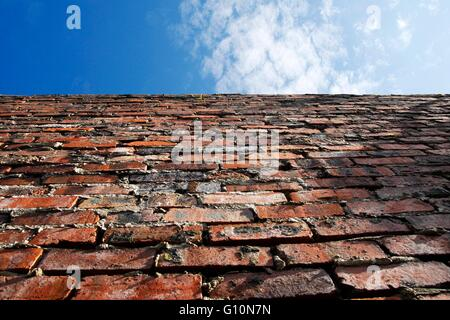 Old brick wall with blue sky above - Stock Photo