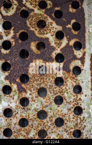Circular holes in a  air vent on a rusted abandoned mine train. Clearwell caves - Stock Photo