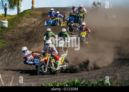 group of motorcyclists with sidecars riding along a dusty track during Cup of Urals motocross - Stock Photo