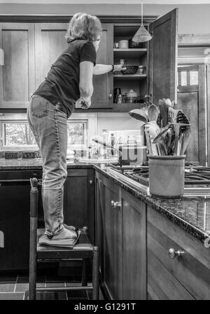 Woman standing on books on chair & reaching into cabinet. Demonstrating fall  risk  for Occupational Therapy safety - Stock Photo