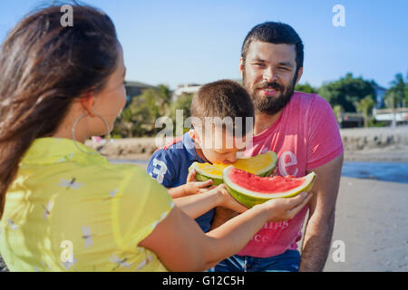 Happy family funny picnic on morning sea beach - mother feed baby boy, adult man. Father, son eat fruits with fun. - Stock Photo
