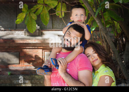 Face portrait of beautiful family - happy mother, father holding baby son on shoulders walk with fun. - Stock Photo