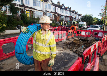 Waste Water Engineer laying pipes in London Street - Stock Photo