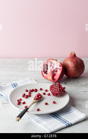 Pomegranate whole and seeds on elegant white plate with wooden spoon and cloth on rustic wooden table. Copy space - Stock Photo