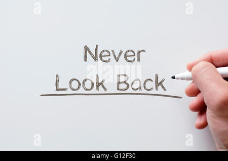 Human hand writing never look back on whiteboard - Stock Photo