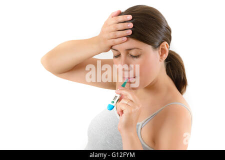 Young woman checking her temperature using oral thermometer - Stock Photo