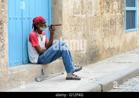 An elderly man sits on a step smoking a large cigar in Old Havana, Havana, Cuba - Stock Photo