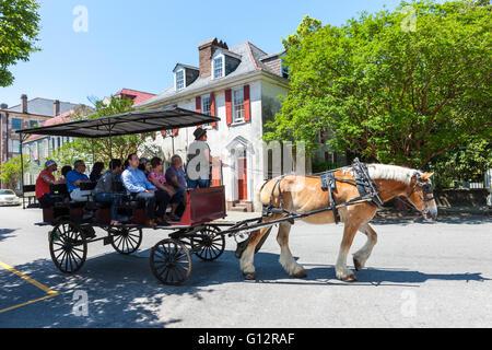 Tourists take a horse-drawn carriage tour past Antebellum homes in historic Charleston, South Carolina. - Stock Photo
