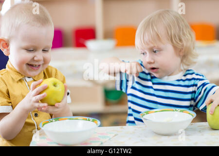 Funny smiling kid eating apple in kindergarten - Stock Photo