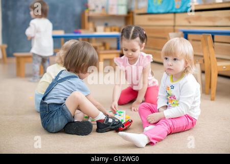 children playing games in kindergarten playroom - Stock Photo