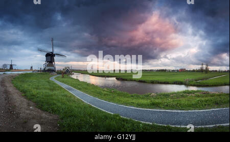 Beautiful landscape with traditional dutch windmills near the famous water canals with dramatic sky, colorful clouds - Stock Photo