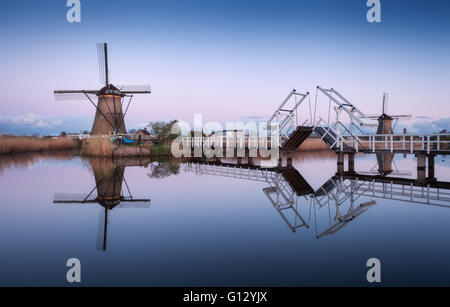 Spring landscape with beautiful traditional dutch windmills near the water channels with reflection in water at - Stock Photo