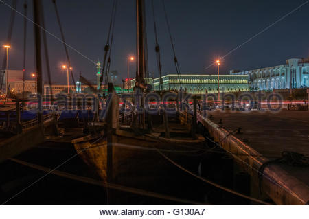 Traditional boats in front of the Amiri Diwan and Grand Mosque on the Doha waterfront at night. - Stock Photo