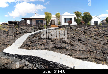 Garden path crossing solidified pahoehoe or ropey lava field to house, Tahiche, Lanzarote, Canary Islands, Spain - Stock Photo