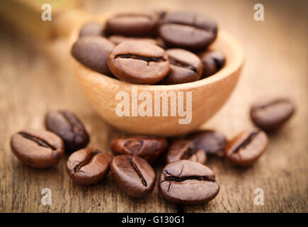 Roasted coffee bean in wooden surface - Stock Photo