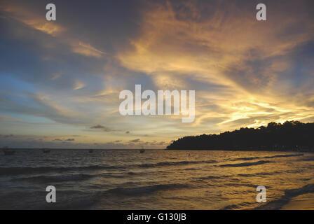 Sunset fishing boats on Ochheuteal Beach in Sihanoukville, Cambodia - Stock Photo