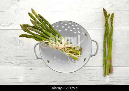 Fresh green asparagus in colander on old wooden background - Stock Photo