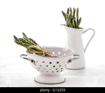 Fresh green asparagus in colander and Jug on old wooden background - Stock Photo