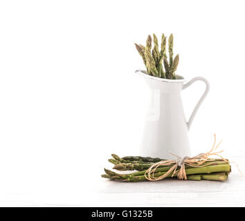 Fresh green asparagus in Jug on old white wooden background - Stock Photo