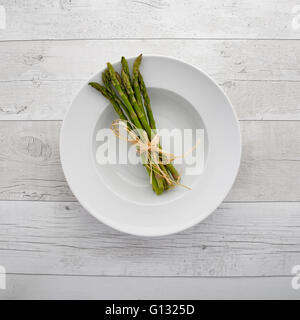 Overhead view of fresh green asparagus on a white plate over a retro wooden background - Stock Photo