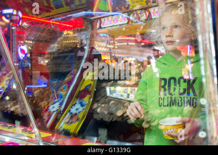 Young girl reflected in the glass of an Amusement arcade on Morecambe seafront, UK - Stock Photo