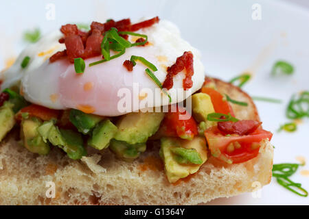 Poached eggs bacon tomatoes and avocado on toast - Stock Photo