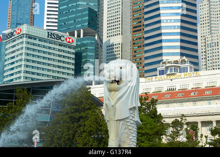 The Merlion Fountain With Luxury Fullerton Hotel And The Singapore Business District Skyline Behind.