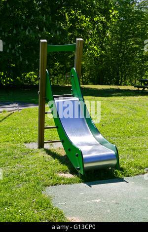 Slide in an empty children's playground in a public park - Stock Photo