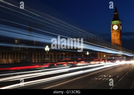 A night shot of Westminster abbey, The Big Ben and London traffic light trails - Stock Photo