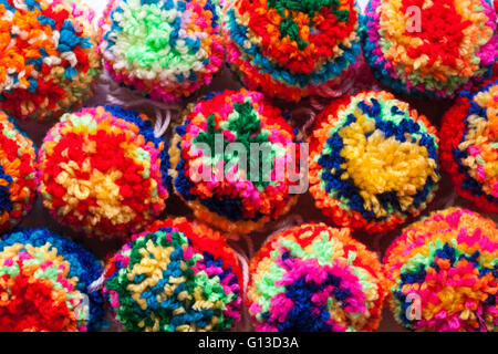 multicoloured home made poms poms made of brightly coloured wool - Stock Photo