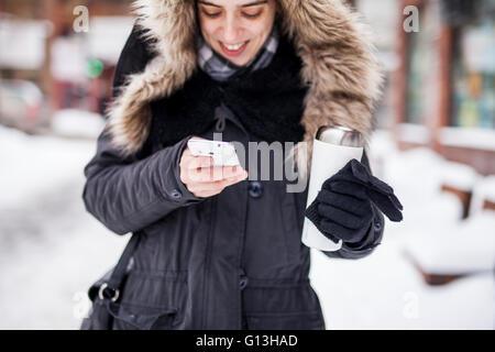 Beautiful woman in urban area using smart phone to communicate - Stock Photo