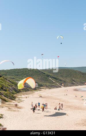 KNYSNA, SOUTH AFRICA - MARCH 3, 2016: Paragliders in the air while beachgoers enjoy the sun at a beach in Buffelsbaai - Stock Photo