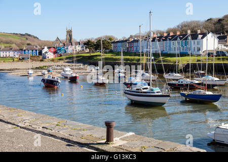 View along Afon Aeron River estuary to church with boats moored in harbour on an incoming tide in coastal town. - Stock Photo